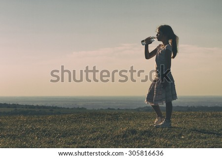 Cute little girl drinking water at sunset.Refreshment for little girl Image is intentionally with grain and toned. - stock photo