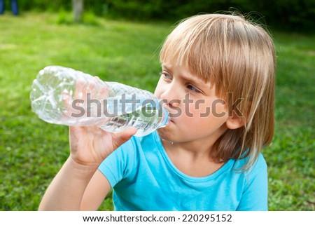 Cute little girl drinking water in a summer garden - stock photo