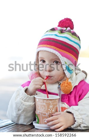 Cute little girl drinks outdoors in cold weather on a white background - stock photo