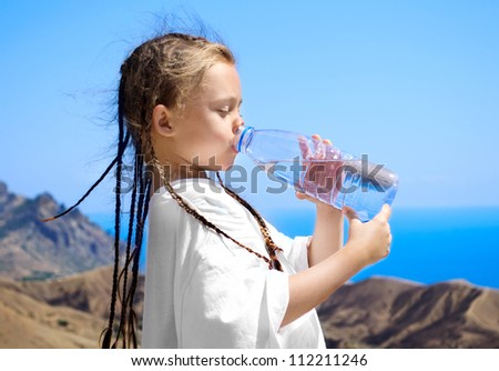cute little girl drinks water from a plastic bottle on the background of blue sea - stock photo