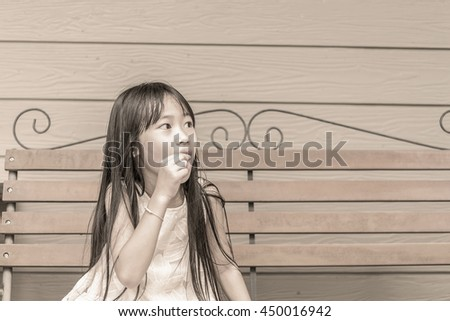 Cute little girl eat snack sit on bench,sepia,vintage style - stock photo