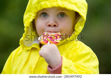 cute little girl eating a lollipop  - stock photo