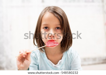 cute little girl eating a red lollipop