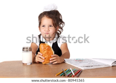 cute little girl eating a snack while drawing - stock photo
