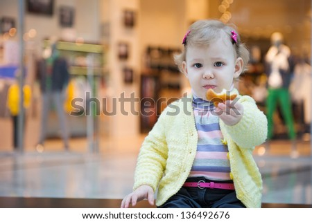 Cute little girl eating biscuit cake on bench in mall - stock photo