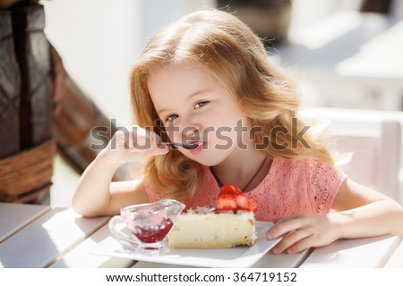 cute little girl eating cake. pretty little girl with cake and strawberries. child eating dessert. girl eating with spoon by the table