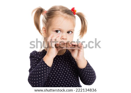 Cute little girl eating chocolate. Two years. - stock photo