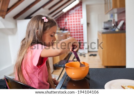 Cute little girl eating from a bowl seated in kitchen at home - stock photo