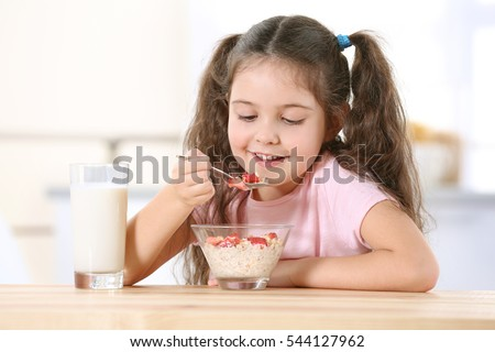 Cute little girl eating healthy breakfast at kitchen table