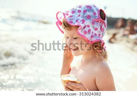 Cute little girl eating ice cream on beach vacation - stock photo