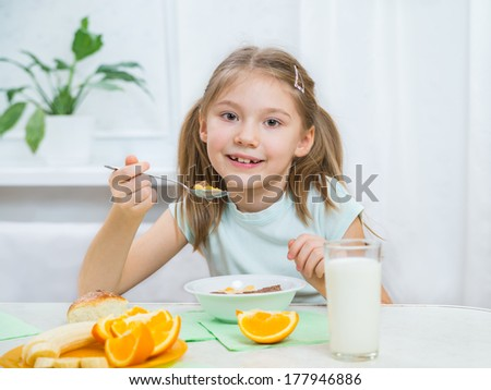 cute little girl eating muesli with fresh fruits - stock photo