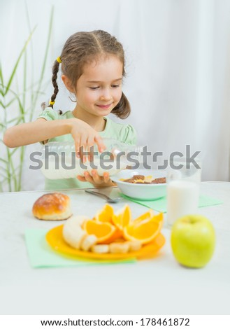 Cute little girl eating muesli with milk and fresh fruits