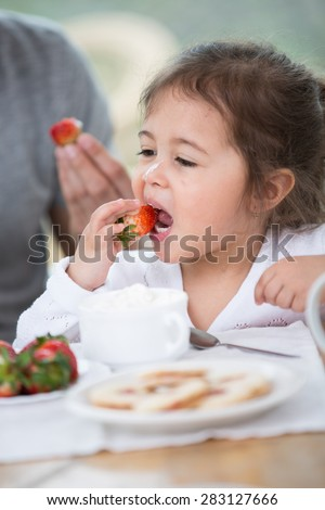 Cute little girl eating strawberry with father at breakfast table - stock photo
