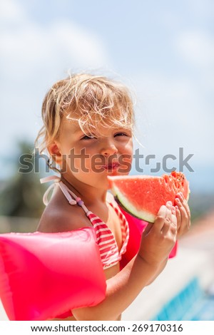 Cute little girl eating water-melon in summertime - stock photo