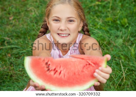 Cute little girl eating watermelon on the grass in summer time. with ponytail long hair and toothy smile sitting on grass and enjoying.  - stock photo