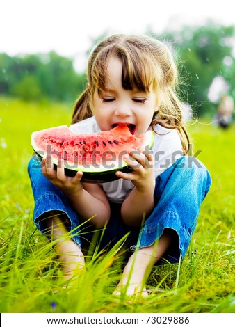 cute little girl eating watermelon on the grass in summertime - stock photo