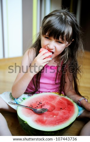 Cute little girl eating watermelon with a spoon on the floor - stock photo