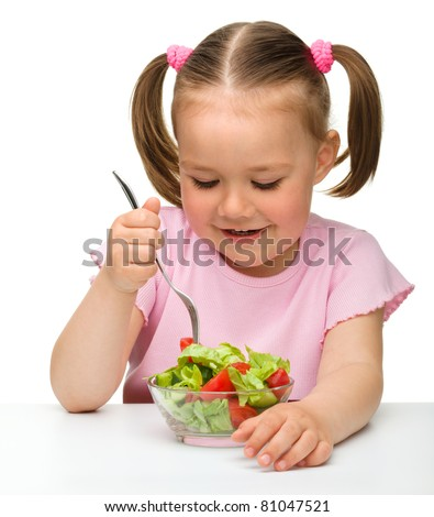 Cute little girl eats vegetable salad using fork, isolated over white - stock photo