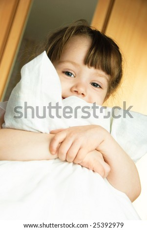 cute little girl embracing a pillow at home in her bedroom