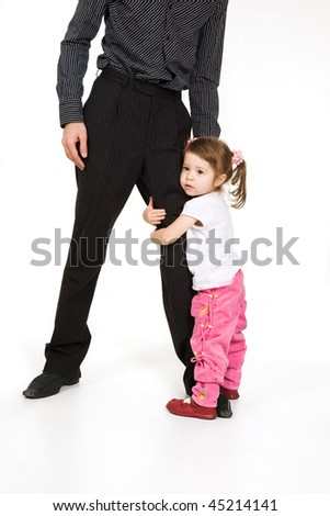 Cute little girl embracing father's leg