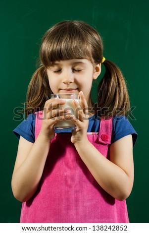 Cute little girl enjoy in glass of milk,I love milk! - stock photo