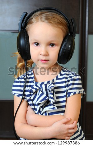 Cute little girl enjoying music using headphones - stock photo