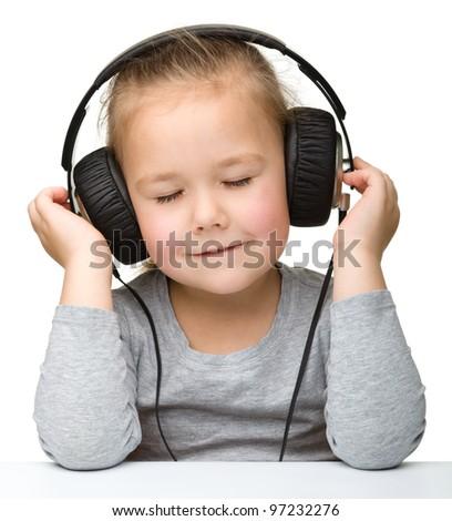 Cute little girl enjoying music using headphones, isolated over white - stock photo