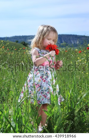 Cute little girl enjoys the smell of flowers on nature, standing in green field - stock photo