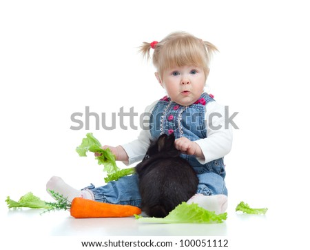 Cute little girl feeding a rabbit with carrot and lettuce on the floor - stock photo