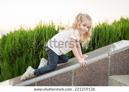 cute little girl for a walk creeps up - stock photo
