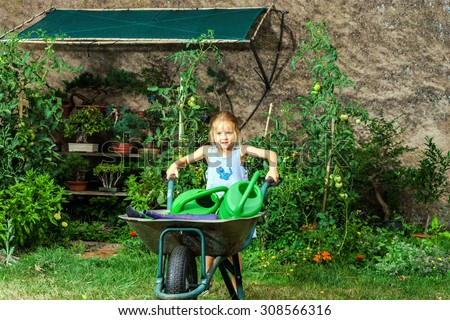 Cute little girl gardening in the backyard. Childhood concept. - stock photo