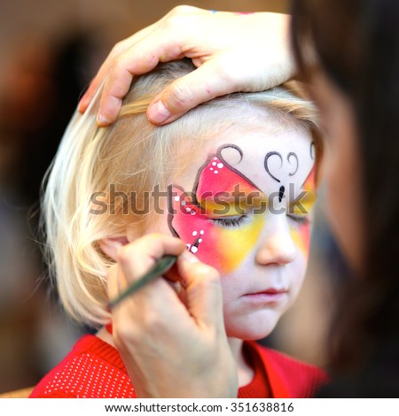 Cute little girl getting her face painted like a butterfly by face painting artist. Kids animation at the party. - stock photo