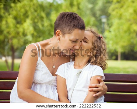Cute little girl giving her mother a kiss. - stock photo
