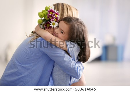 Cute little girl greeting her mother at home. Mother's day concept