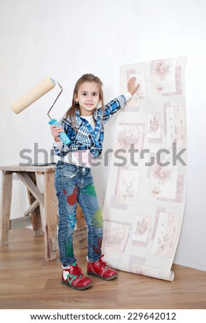 Cute little girl hanging wallpaper. Decorating the wall - stock photo