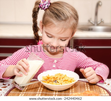 Cute little girl having breakfast cereals with milk in the kitchen - stock photo