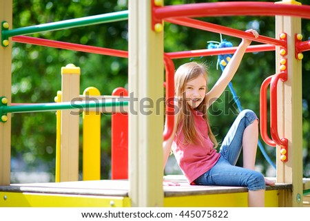 Cute little girl having fun on a playground outdoors in summer - stock photo