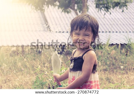 Cute little girl having fun play water in the garden in vintage color - stock photo