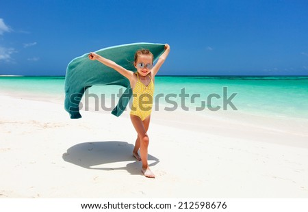 Cute little girl having fun running with towel and enjoying vacation at tropical beach on white sand and turquoise ocean water