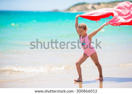 Cute little girl having fun running with towel on tropical beach with white sand and turquoise ocean water - stock photo