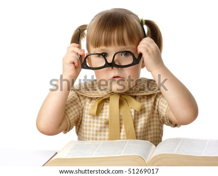Cute little girl having fun with big book wearing black glasses, back to school concept, isolated over white - stock photo