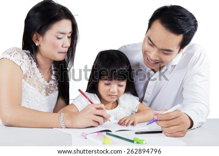 Cute little girl helped by her parents to write on the book, isolated on white background