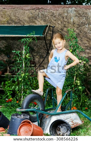 Cute little girl helping her mother in the backyard with heavy wheelbarrow