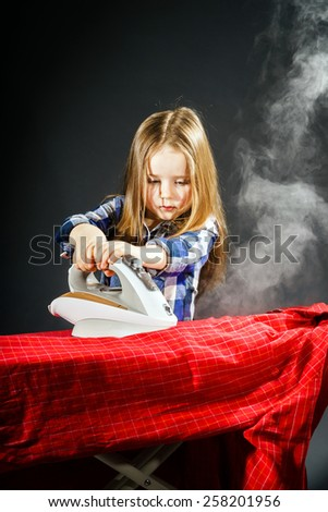 Cute little girl helping your mother by ironing clothes, childhood concept - stock photo
