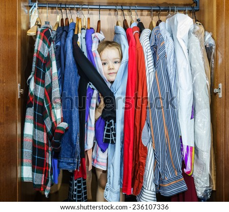 Cute little girl hiding inside wardrobe from her parents early morning - stock photo