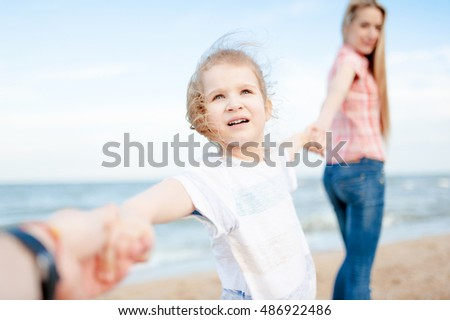 Cute little girl hold hands of their parents and stand at the beach. Holiday and travel.