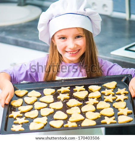 cute little girl holding a baking sheet of cookies - stock photo
