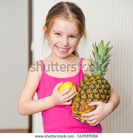 cute little girl holding a pineapple and lemon - stock photo