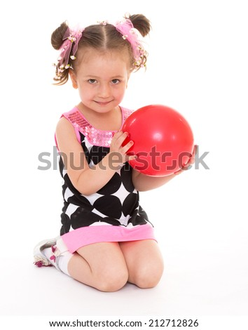 cute little girl holding a red ball on a white background.The concept of development of the child younger years. - stock photo
