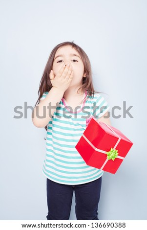 cute little girl holding a red gift box blowing a kiss to you on blue background